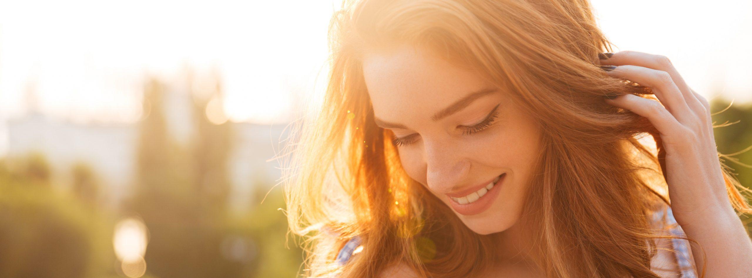 Lächelnde Rothaarige im Sonnenlicht